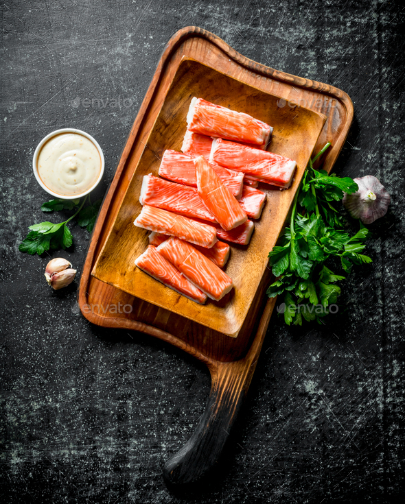 Crab sticks on a cutting Board with greens, sauce and garlic. - Stock Photo - Images