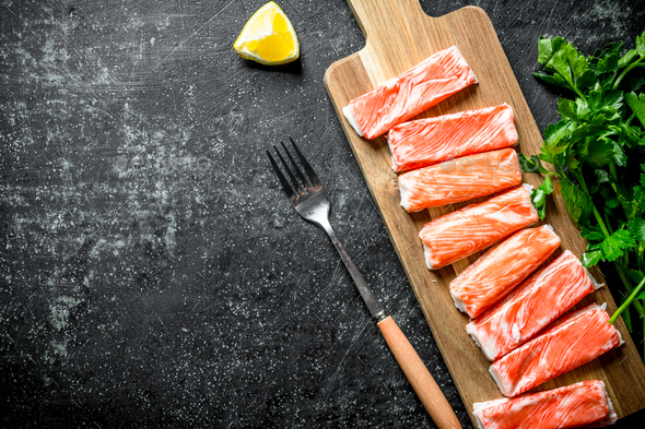 Crab sticks on a chopping Board with parsley and lemon. - Stock Photo - Images