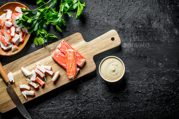 Sliced crab sticks with sauce and herbs. - Stock Photo - Images