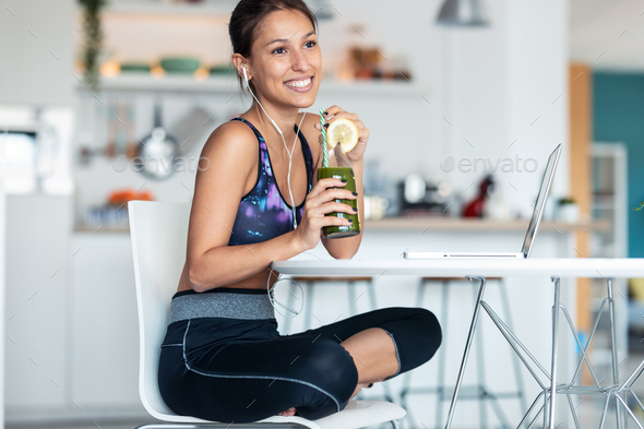 Sporty woman drinking detox juice while working with laptop after exercises in the kitchen at home. - Stock Photo - Images