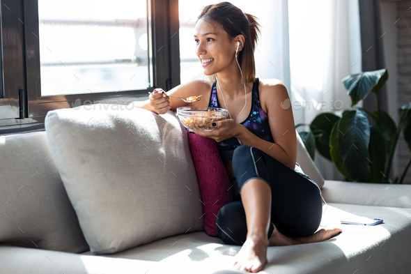 Sporty young woman eating a bowl of muesli while listening music sitting on the couch at home. - Stock Photo - Images