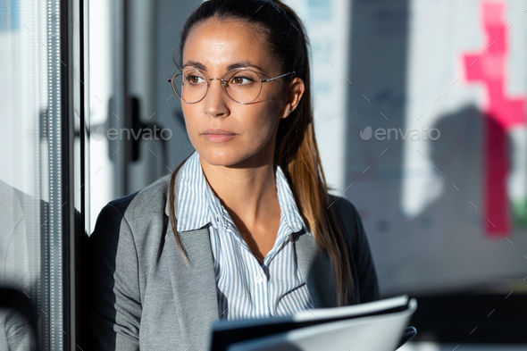 Concentrated young woman reading some documents while looking through the window in the office. - Stock Photo - Images
