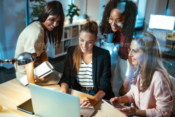 Four businesswomen talking and reviewing the latest work done on the computer in a joint workspace. - Stock Photo - Images
