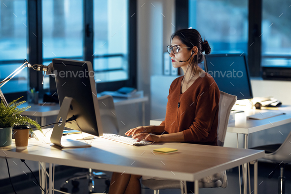 Beautiful business woman working with computer while talking with earphone sitting in the office. - Stock Photo - Images