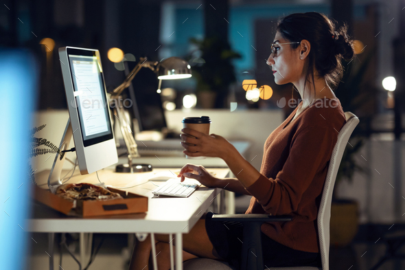 Beautiful young business woman working with computer while drinking coffee sitting in the office. - Stock Photo - Images