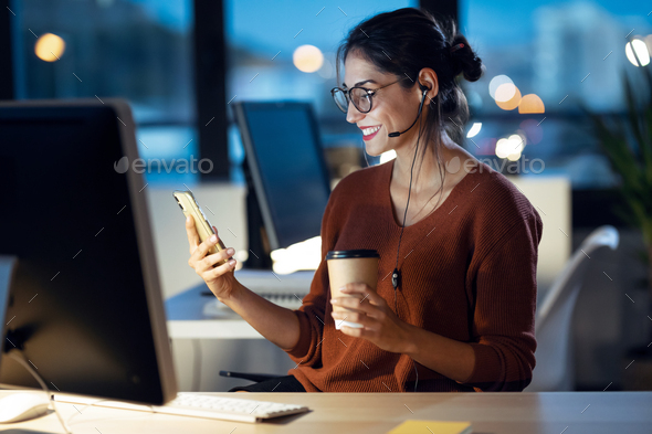Beauty business woman having videocall with mobile phone while working with computer in the office. - Stock Photo - Images