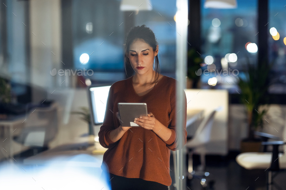 Smart pretty business woman taking a break cheaking her digital tablet in the office. - Stock Photo - Images