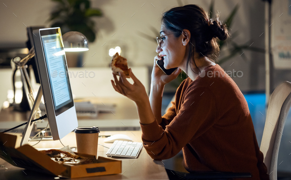 Beautiful young business woman working with computer while eating pizza sitting in the office. - Stock Photo - Images