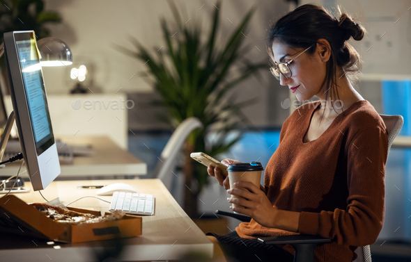 Beauty business woman sending messages with mobile phone while working with computer in the office. - Stock Photo - Images