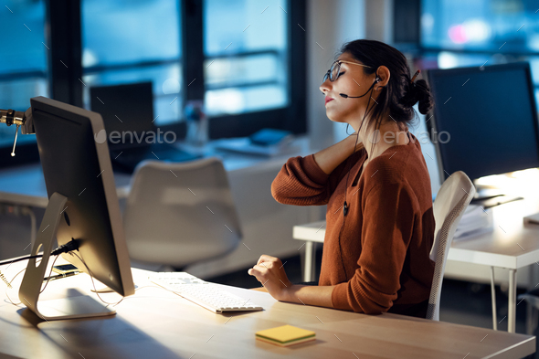 Tired business woman with back pain looking uncomfortable while working with computer in the office. - Stock Photo - Images
