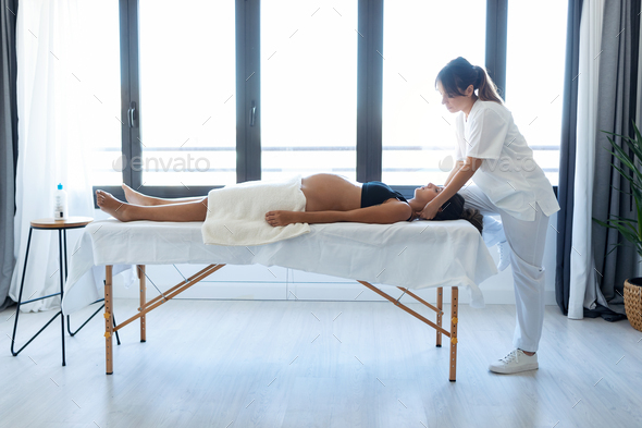 Beauty physiotherapist doing osteopathic treatment in pregnant woman's neck on a stretcher at home. - Stock Photo - Images