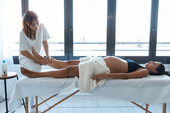 Beautiful young physiotherapist massaging the pregnant woman's legs on a stretcher at home. - Stock Photo - Images