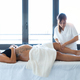 Beautiful young physiotherapist massaging the pregnant woman's legs on a stretcher at home. - PhotoDune Item for Sale