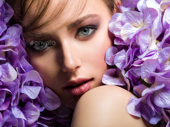 Pretty woman with bright makeup. Beautiful white girl with purple flowers. - Stock Photo - Images