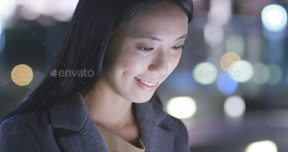 Asian Woman looks at mobile phone in city - Stock Photo - Images