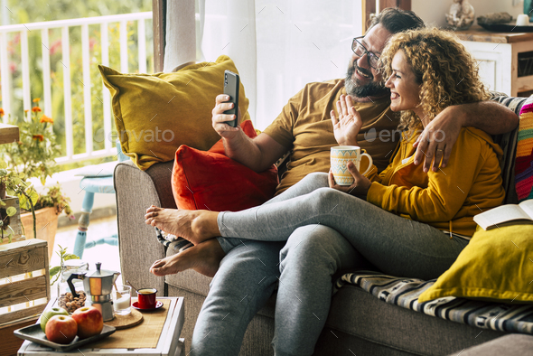 Adult happy couple man and woman at home enjoy morning breakfast and do video phone call - Stock Photo - Images