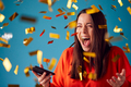 Celebrating Young Woman With Mobile Phone Winning Prize And Showered With Gold Confetti In Studio - PhotoDune Item for Sale
