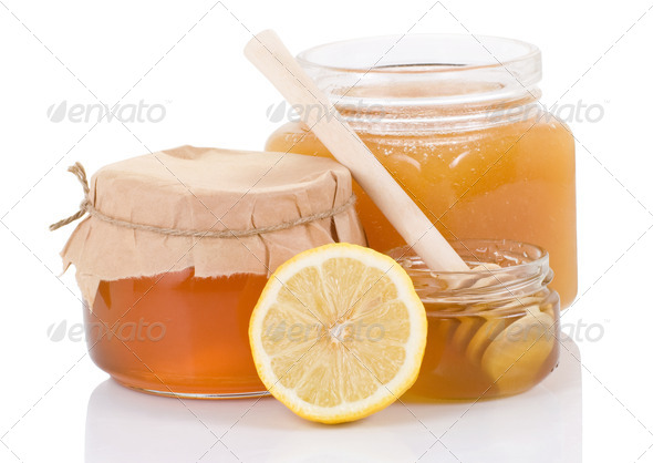 pot full of honey and lemon isolated on white - Stock Photo - Images