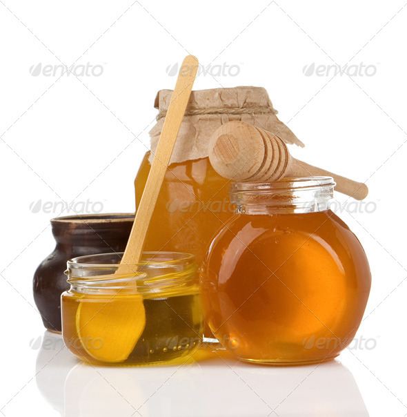glass pot full of honey isolated on white - Stock Photo - Images