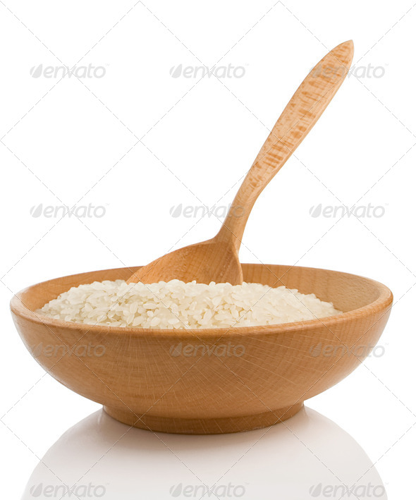 rice in plate and wooden spoon on white - Stock Photo - Images
