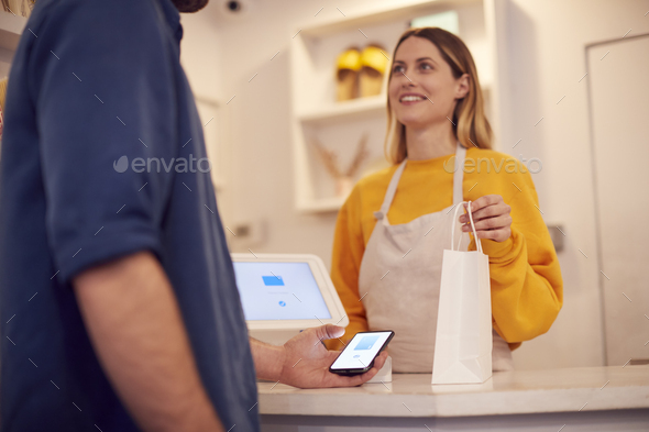 Female Small Business Owner Accepting Contactless Payment In Shop From Customer Using Mobile Phone - Stock Photo - Images