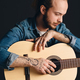 Tattooed musician posing with guitar over black background. Stylish guy with acoustic guitar - PhotoDune Item for Sale