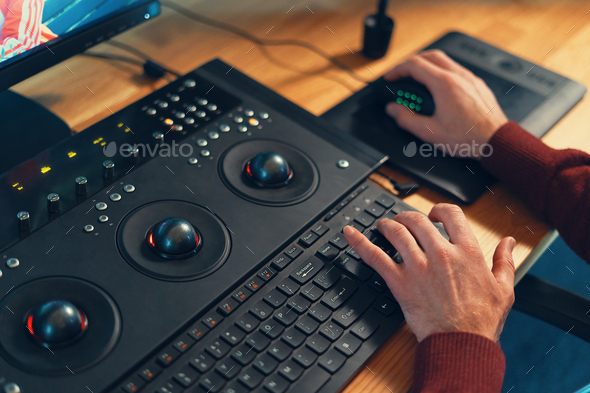 Video editor hands adjusting color or sound on working console machine - Stock Photo - Images