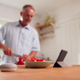 Retired Man Making Meal In Kitchen With Smart Speaker In Foreground - PhotoDune Item for Sale