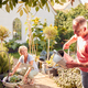 Retired Couple At Work Watering And Caring For Plants In Garden At Home - PhotoDune Item for Sale