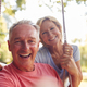 Portrait Of Retired Couple Having Fun With Woman Pushing Man On Garden Swing - PhotoDune Item for Sale