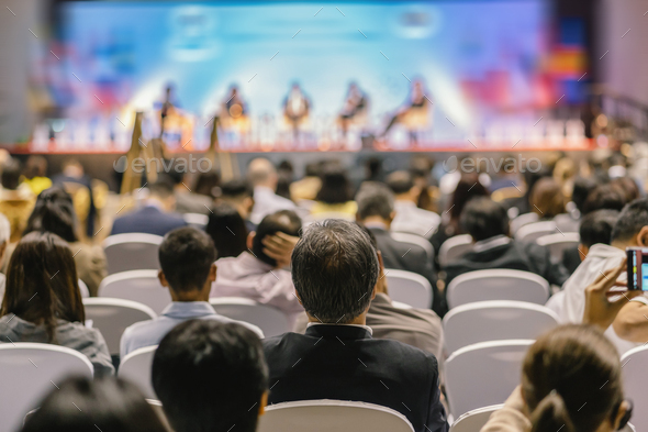 Rear view of Audience listening Speakers on the stage in the conference hall or seminar meeting - Stock Photo - Images