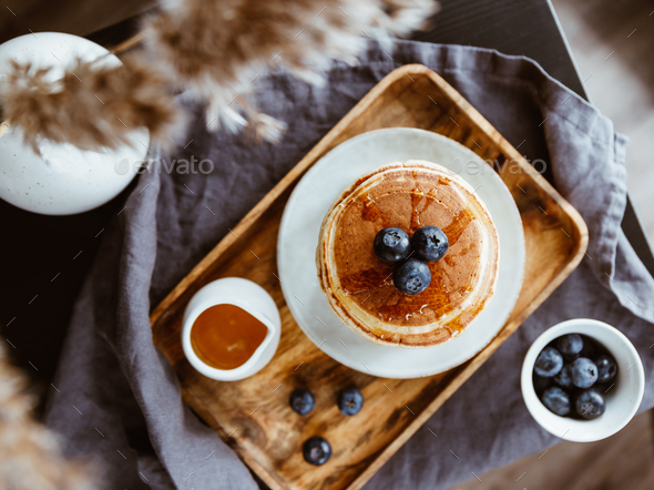 Top view of American traditional pancakes with honey and fresh blueberry - Stock Photo - Images