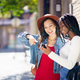 Two friends looking at their smartphone together. Multiethnic women - PhotoDune Item for Sale