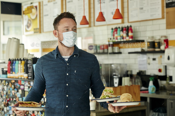 Waiter wearing mask holding two plates of food for customers - Stock Photo - Images