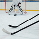 Hockey sticks held by two players in sports uniform on background of goal keeper - PhotoDune Item for Sale