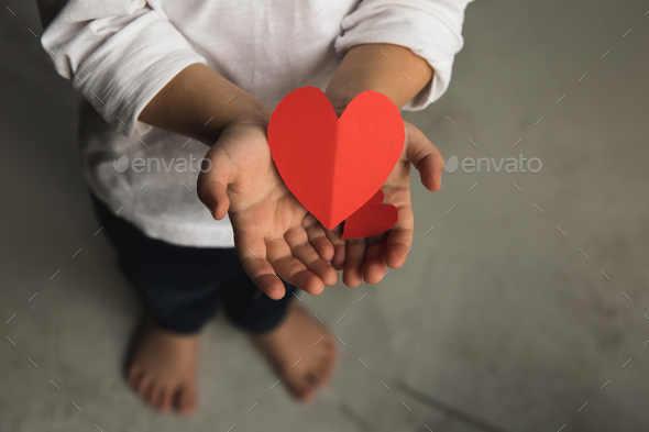 Two baby hands holding red paper hearts. - Stock Photo - Images