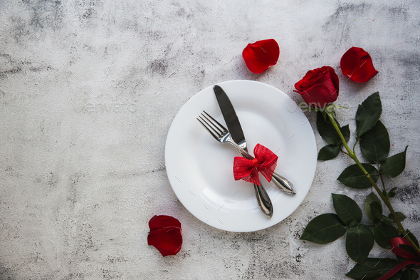 Festive table setting with red roses for valentines day. - Stock Photo - Images
