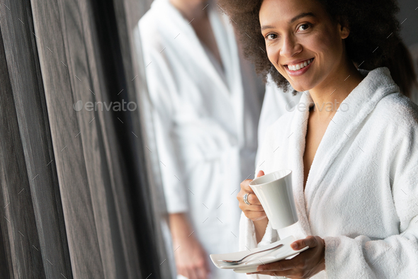 Woman in bathrobes enjoying tea during wellness weekend - Stock Photo - Images