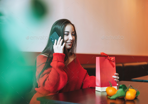 Beautiful smiling young asian woman in red sweater with gift bag using mobile in cafe - Stock Photo - Images