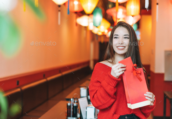 Asian woman in red clothes with red gift bag in restaurant celebrating Chinese New Year - Stock Photo - Images