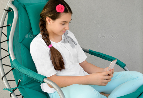 Young girl texting a message on her mobile - Stock Photo - Images