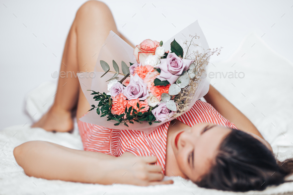 A woman holding a large mix of a bouquet of different flowers in her hands - Stock Photo - Images