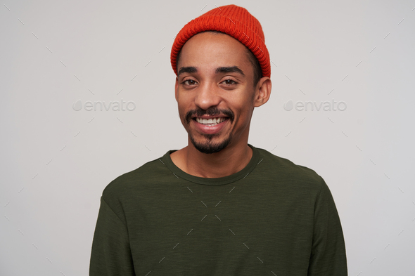 Portrait of beautiful young brown-eyed dark skinned male with beard looking cheerfully at camera - Stock Photo - Images