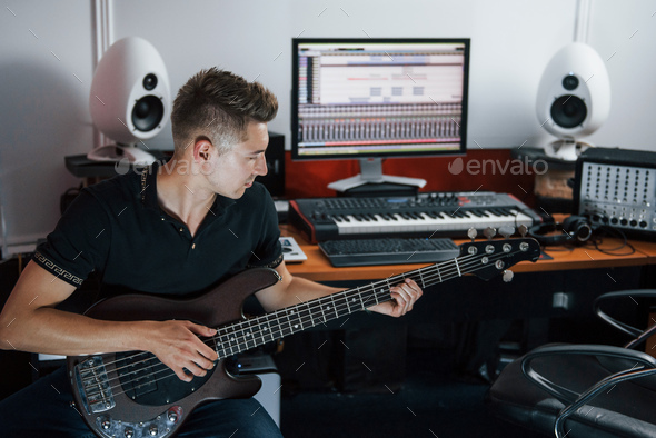 Young musician records bass guitar indoors in the studio - Stock Photo - Images