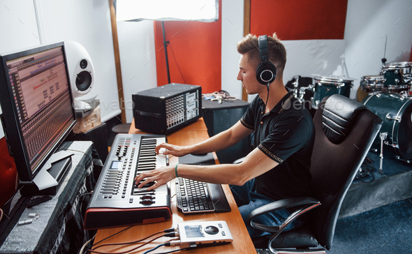 Sound engineer in headphones working and mixing music indoors in the studio - Stock Photo - Images