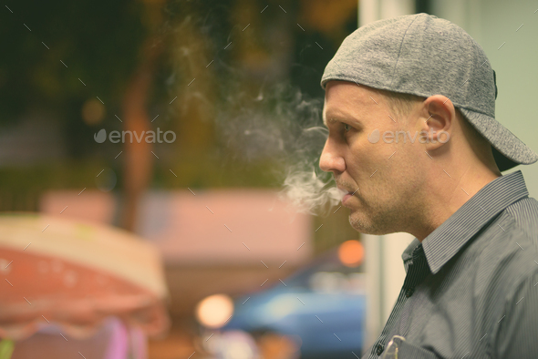 Mature man smoking electronic cigarette in the streets at night - Stock Photo - Images