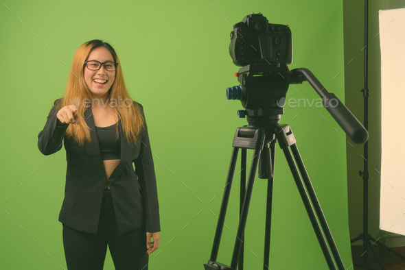 Young Asian businesswoman against green background - Stock Photo - Images