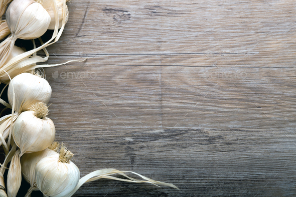 String of garlic on wooden board background, copy space - Stock Photo - Images
