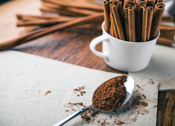 Cinnamon sticks and powder on rustic wooden board close up - Stock Photo - Images