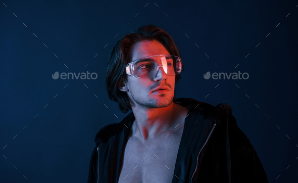 Beautiful long haired hot man in glasses is in the studio with blue neon lighting - Stock Photo - Images